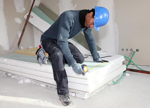 Worker Measuring a Drywall